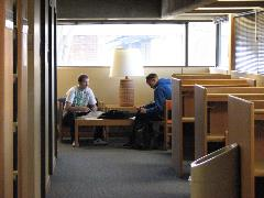 Two people studying in the library